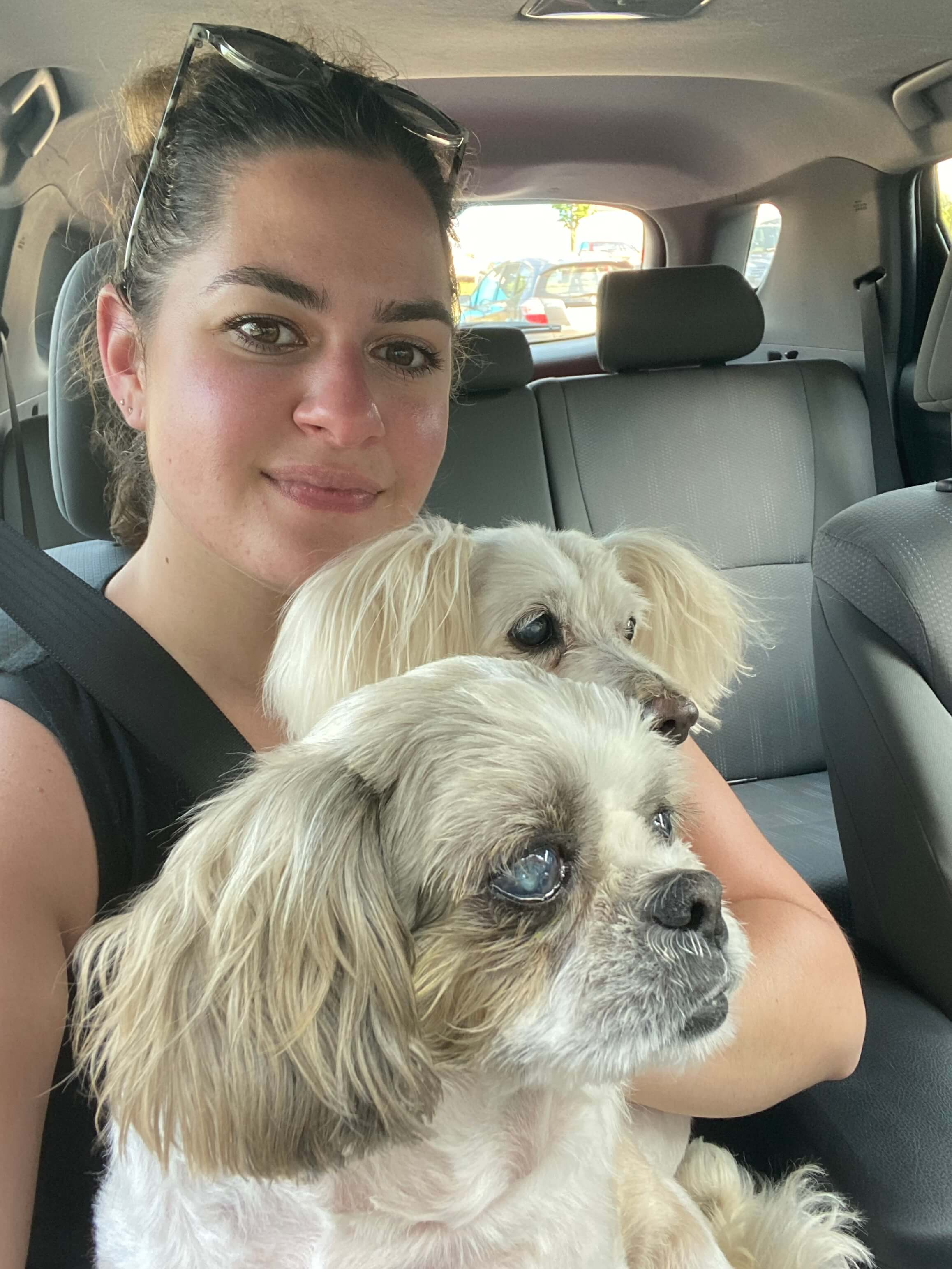 Jessica Leblond with her two dogs in a passenger seat in a car