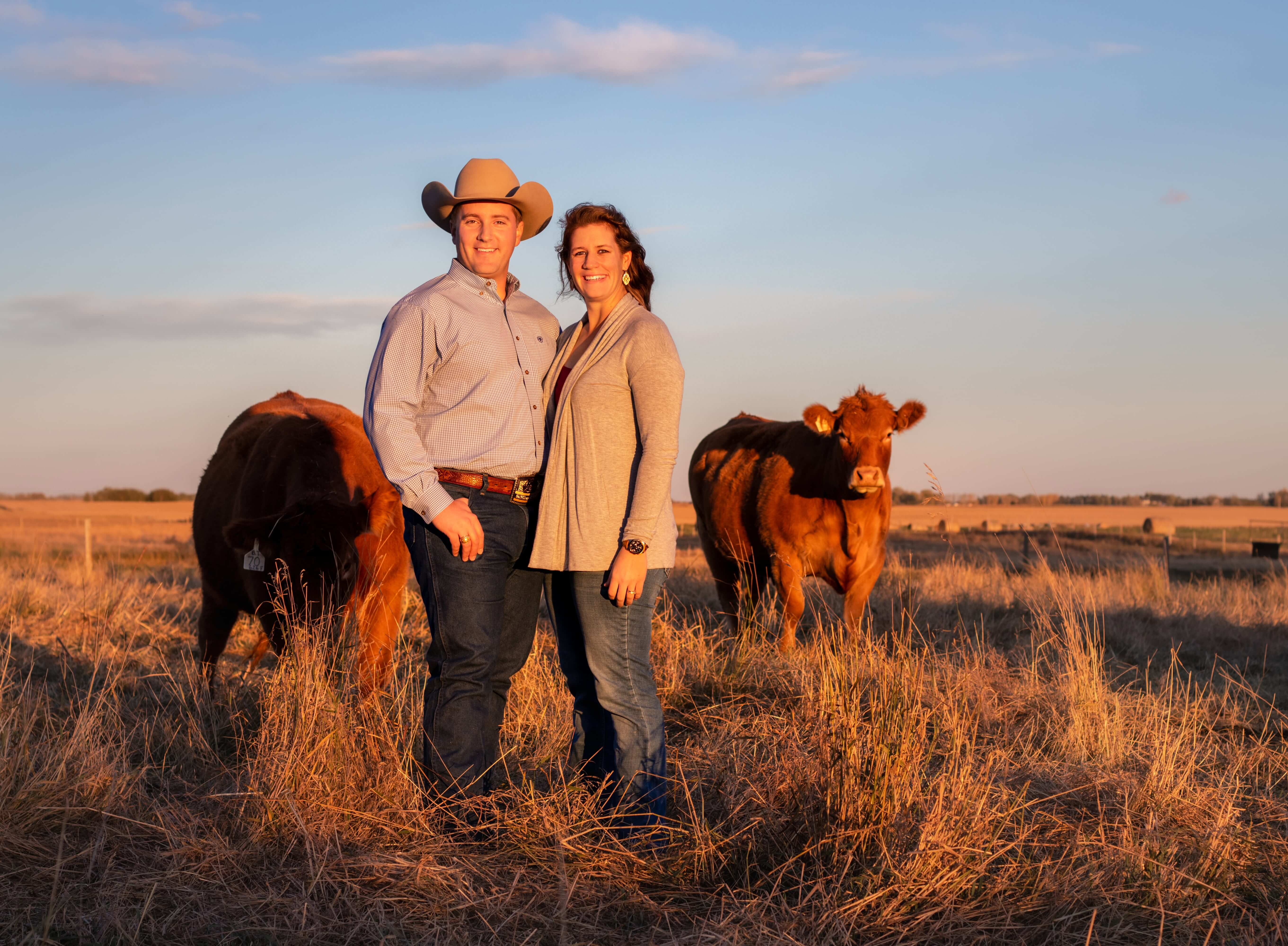 Rosie Dwight with her husband standing in the farm field