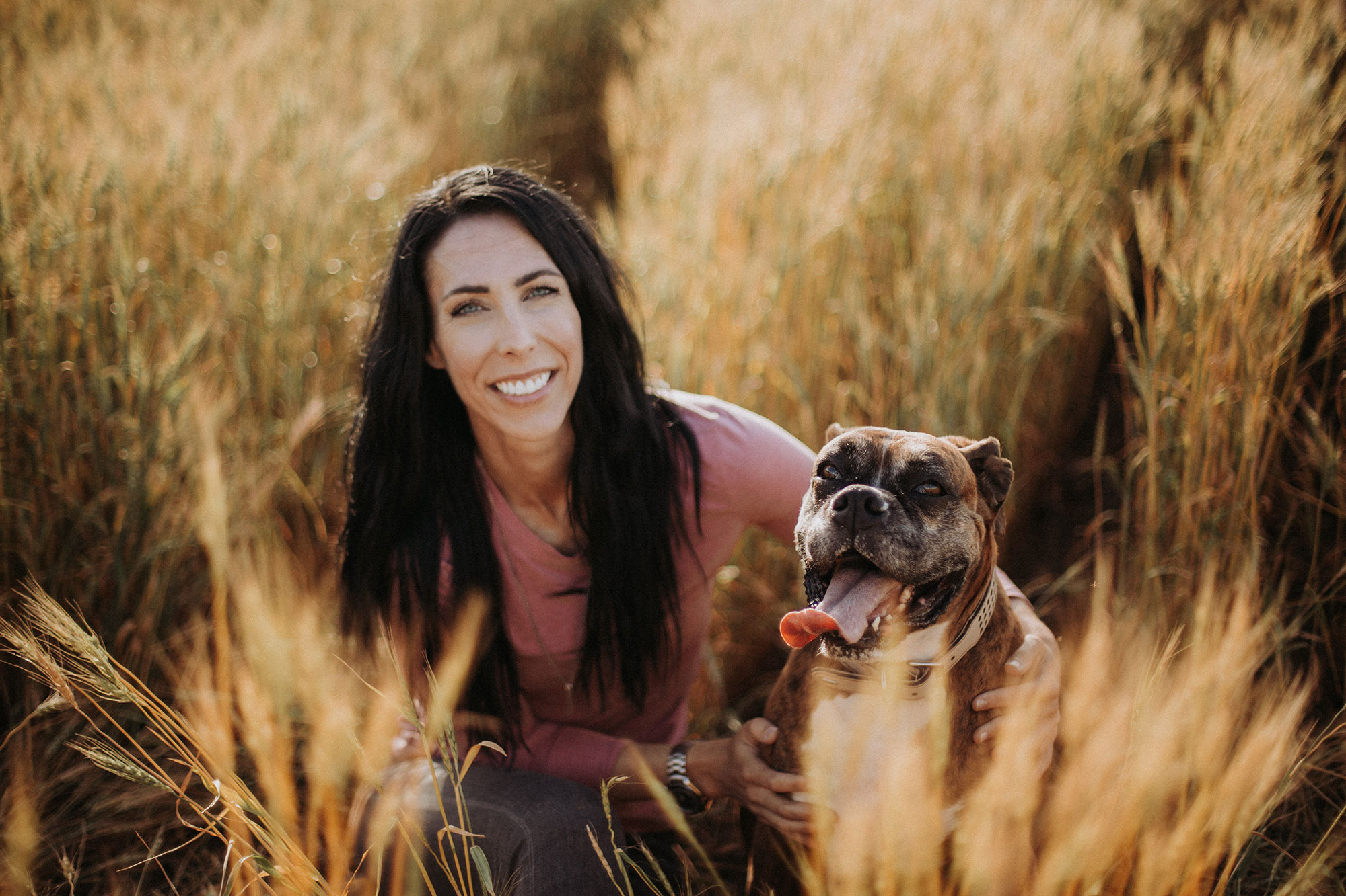 Kim Keller smiling in a field with her dog.