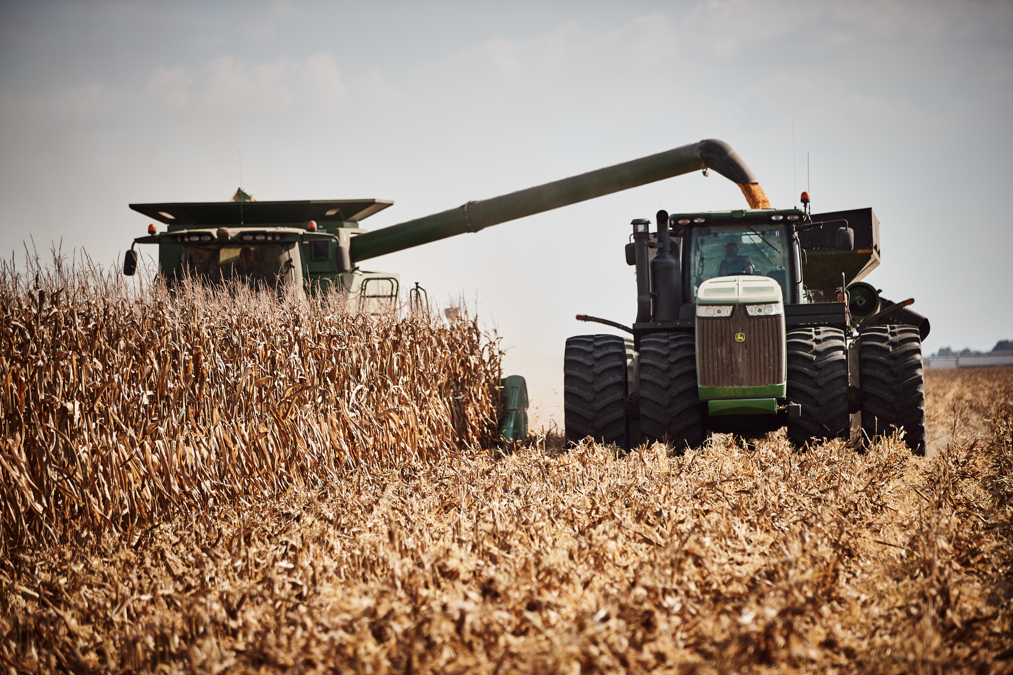 A combine harvester working along tractor pulled trailer to gather crops