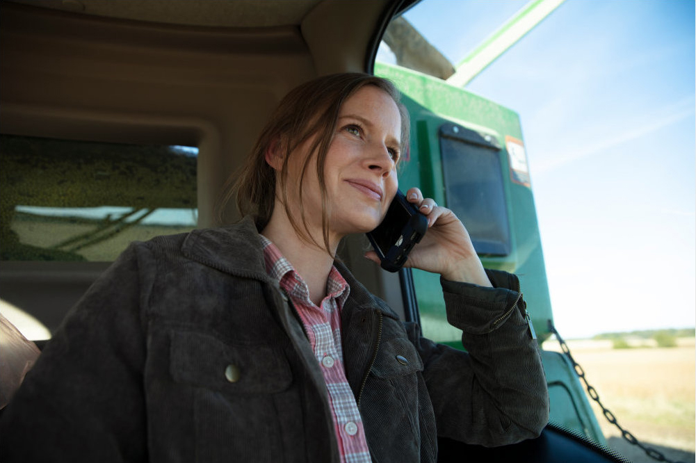 Woman in a tractor having a conversation over the phone.