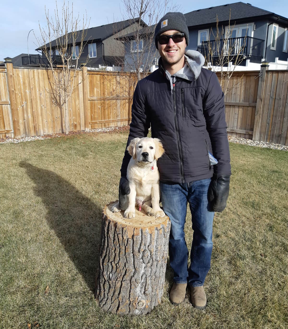 Mat Vercaigne with his puppy standing on a log in his backyard