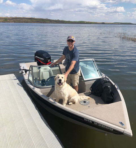 Mat Vercaigne on a motor boat with his dog