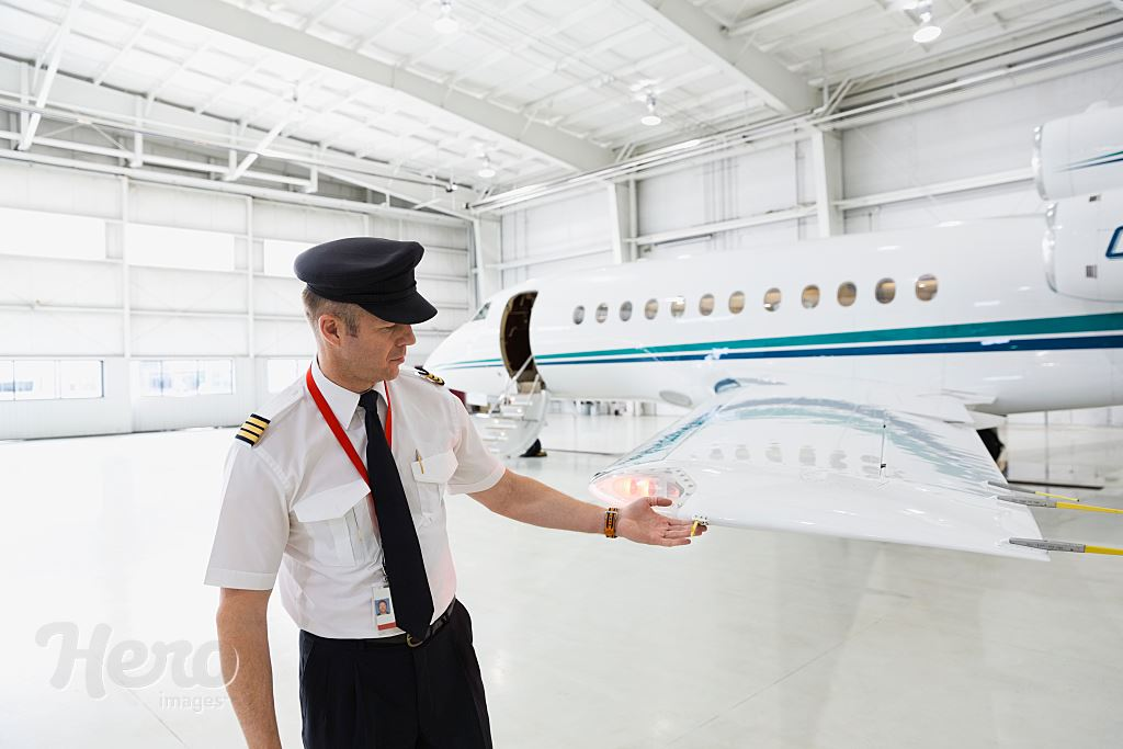 Male pilot checking airplane wing in hangar | Hero Images