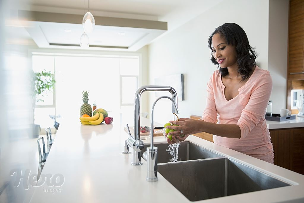 Pregnant Woman Washing Grapes At Kitchen Sink Hero Images
