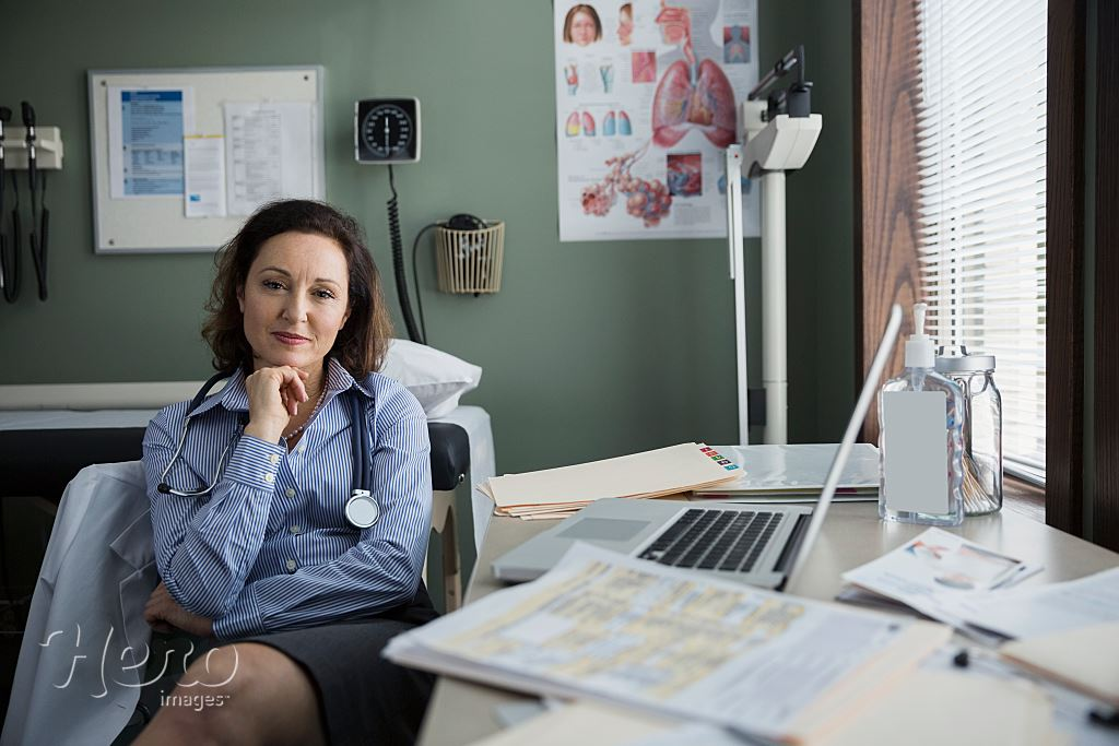 03244c34b4 smiling, portrait, caucasian, sitting, laptop, looking at camera, one  person, desk, three quarter length, doctor, healthcare, posing, brunette,  clinic, ...