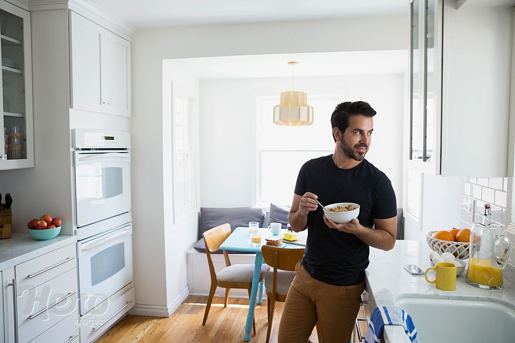 Man eating cereal and looking away in kitchen | Hero Images
