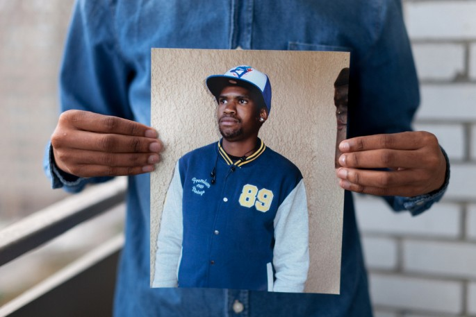 Colin Boyd Shafer, </span><span><em>Melvyn (Born in Botswana) holding a photograph of his late brother</em>, </span><span>2014