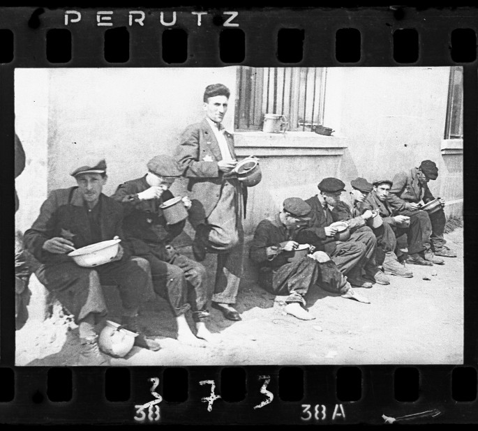 """Henryk Ross, </span><span><em>Lodz ghetto: """"Soup for lunch"""" (Group of men alongside building eating from pails)</em>, </span><span>1940-44 Art Gallery of Ontario Gift from Archive of Modern Conflict, 2007 © Art Gallery of Ontario"""