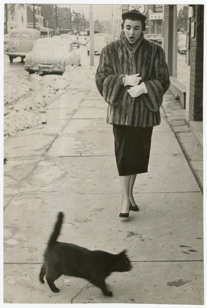 Unidentified photographer, To have a black cat cross your path at any time is unfortunate, but on Friday the 13th – oh, my! – which is just what Jean Craig said, 1953. Gelatin silver print, 9 x 6. Gift of The Globe and Mail newspaper to the Canadian Photography Institute of the National Gallery of Canada.