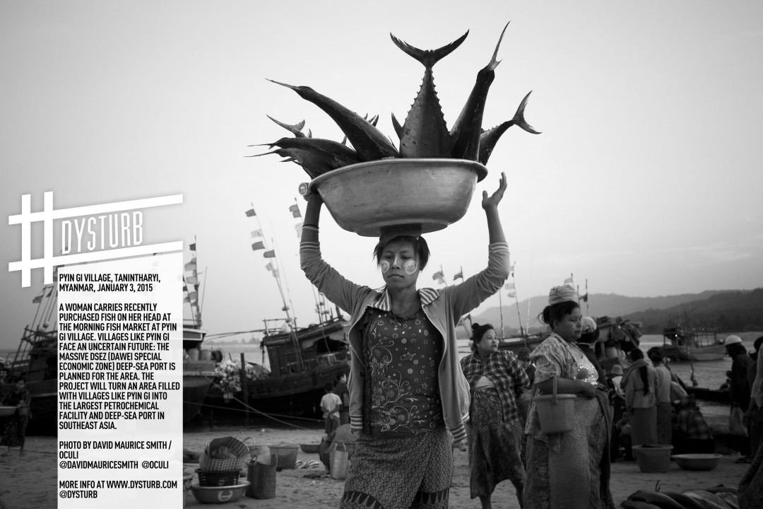 David Maurice Smith, Pyin Gi Village, Tanintharyi, Myanmar. January 3, 2015. A woman carries recently purchased fish on her head at the morning fish market at Pyin Gi Village. Villages like Pyin Gi face an uncertain future as the development of the massive DSEZ (Dawei Special Economic Zone) deep sea port will impact the area on many levels. The project will turn an area filled with villages like Pyin Gi into the largest petrochemical facility and deep sea port in Southeast Asia. Courtesy of Oculi.