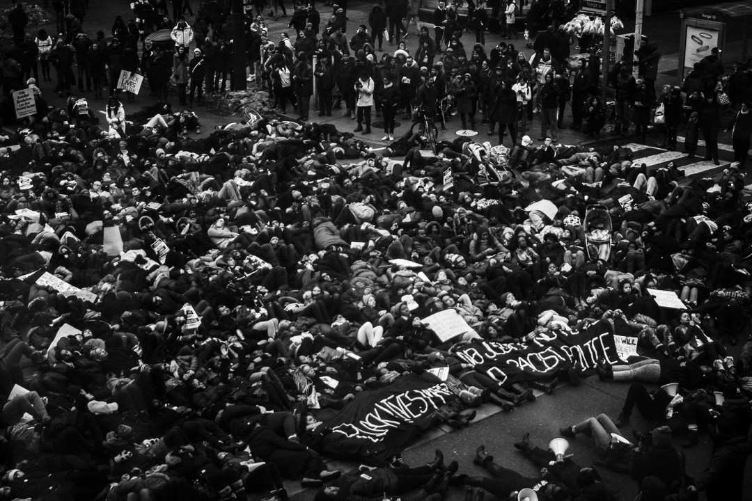 Jalani Morgan, Black Lives They Matter Here (The power of symbolism: protesters perform a 'die-in' by laying on the ground at Yonge and Dundas Square in Toronto. This was in soli- darity and in rage of the decision of the New York grand jury to not indict the police officers responsible for the murder of Eric Garner), Toronto, Canada., 2014. Inkjet print on vinyl, 8.7x6.5. Courtesy of the artist.
