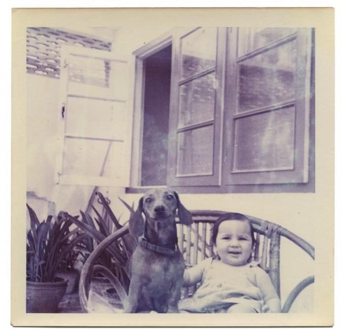 """Anil Dewan, </span><span><em>Deepali with her dog on a wicker garden chair, New Delhi, India</em>, </span><span>1972. Dye coupler print, 3.4 x 3.4"""". Courtesy of Deepali Dewan."""