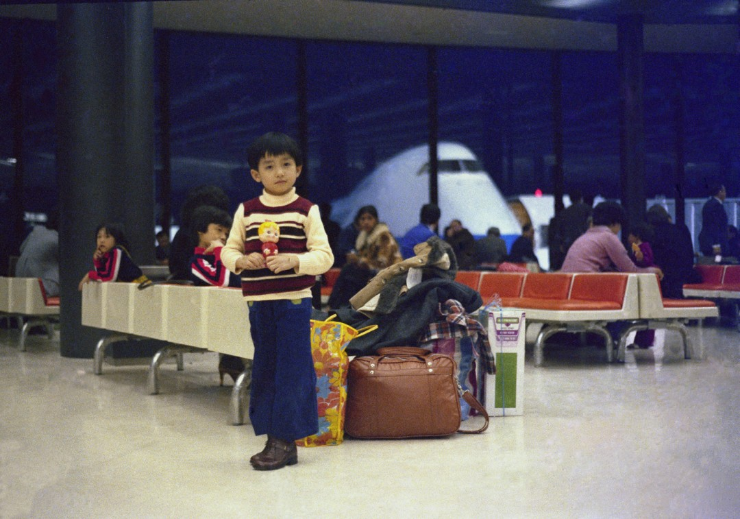 Luong Thai Lu, Hon standing in the Narita International Airport during a stop-over on the way to Canada, surrounded by the family's luggage, Narita, Japan, March 1979. Gift of the Lu-Thai Family.