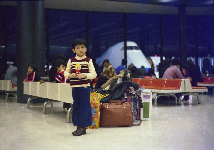 Luong Thai Lu, </span><span><em>Hon standing in the Narita International Airport during a stop-over on the way to Canada, surrounded by the family's luggage, Narita, Japan</em>, </span><span>March 1979. Gift of the Lu-Thai Family.