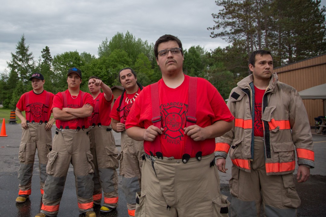 Allen Agostino, Garden River Reserve, Ontario, Canada. Members of the Garden River Fire Department discuss strategy in between events during the annual Ontario Native Firefighters Competition., June 4, 2016