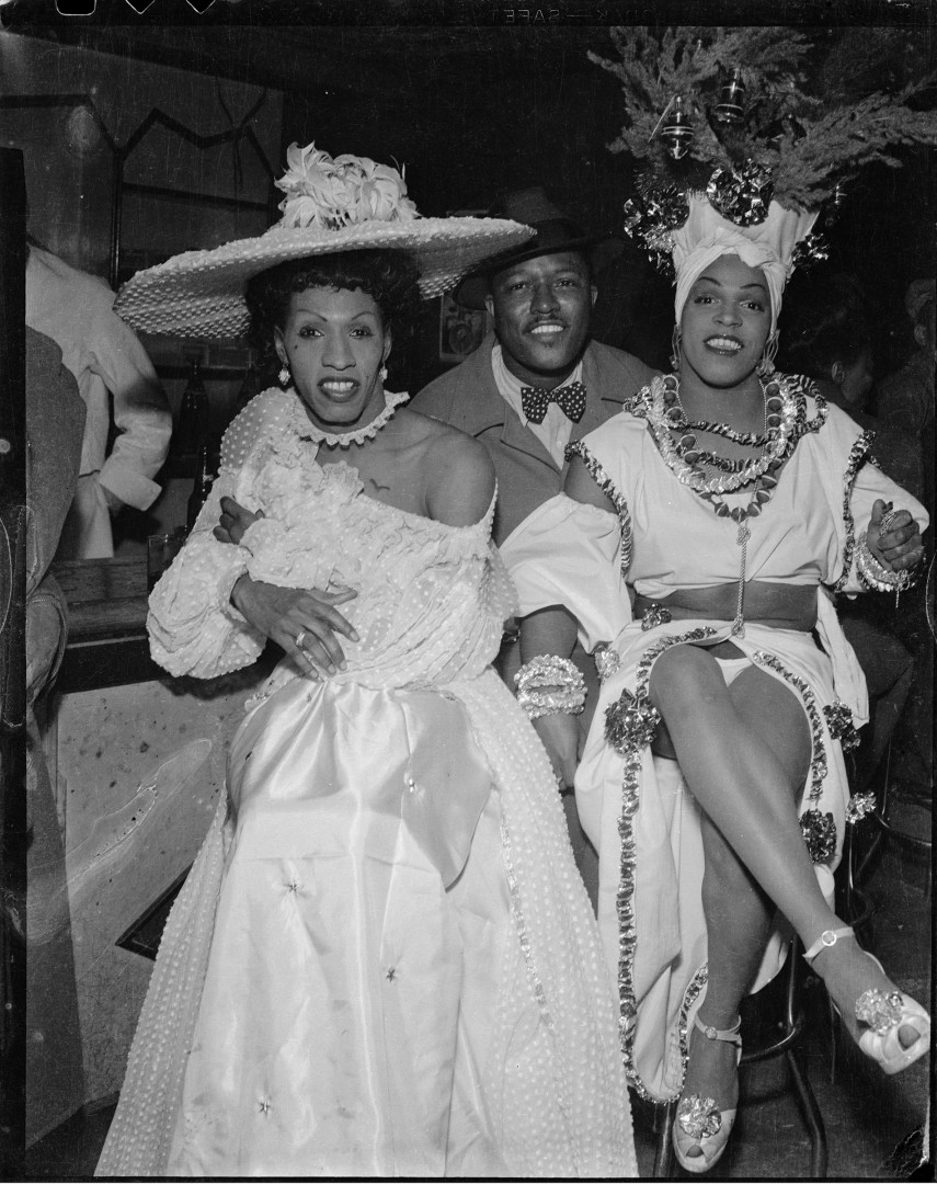 "Charles ""Teenie"" Harris, </span><span><em>Man seated between drag performers &quot;Gilda,&quot; and &quot;Junie&quot; Turner wearing Caribbean-style costume</em>, </span><span>1945 – 1955.