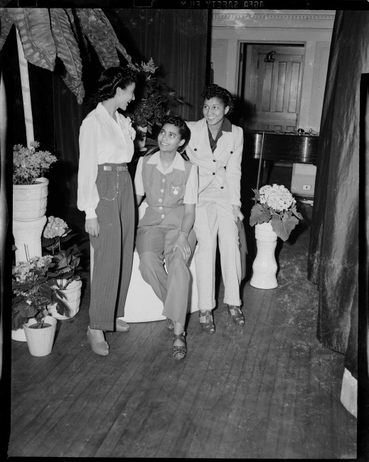 "Charles ""Teenie"" Harris, </span><span><em>Three women wearing pants, pictured at the Beauty Shop Owners\' Fashion Review in Schenley High School</em>, </span><span>1945. Silver Gelatin print. Courtesy of Carnegie Museum of Art, Pittsburgh"