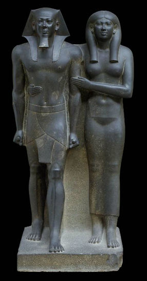 Stylized statue of a man and a woman standing next to one another. Both are very static. The rock between the two figures has not been removed to give the statue stability