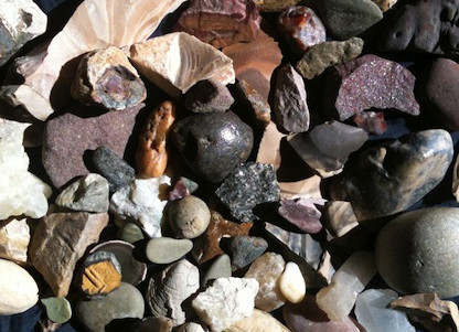 A variety of stones with differing colors, textures, and sizes. Overall the color pallet is muted, but there are some brighter reds and greens.