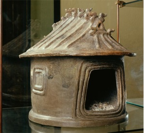 The urn has a large opening in the front and the top is shaped like a roof .