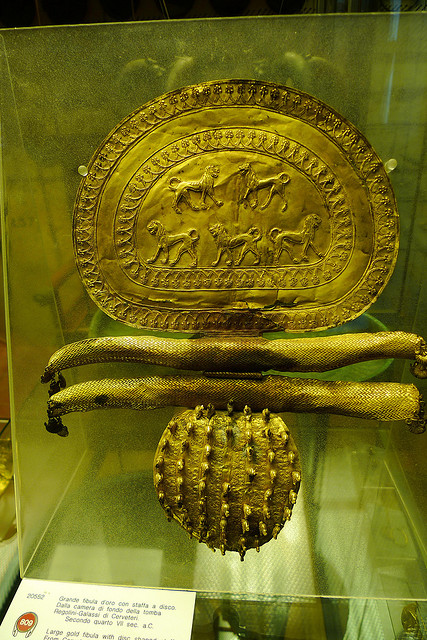 Ornate gold jewelry piece; There are intricate carvings on the upper portion depicting carnivorous animals
