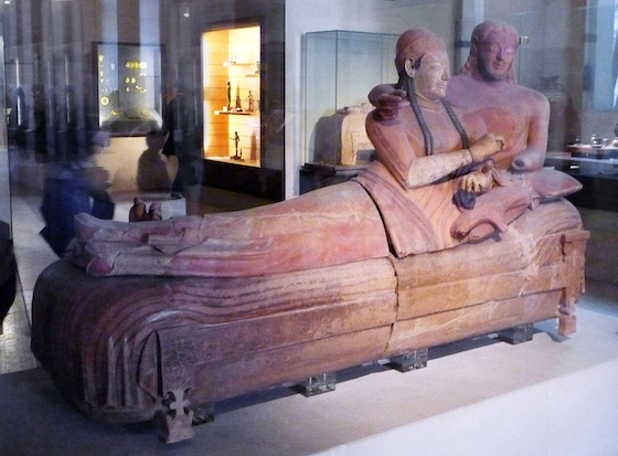 A sarcophagus adorned with a sculpture of a man and a woman lounging with one another on top of the sarcophagus.