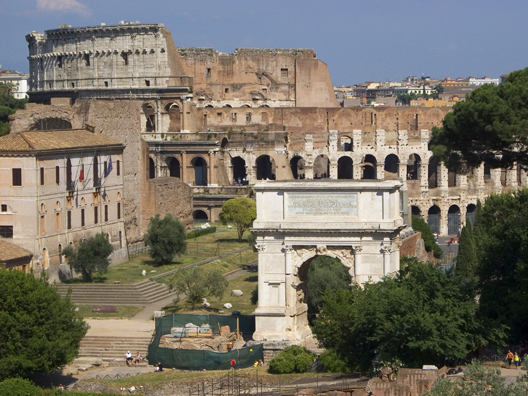Both iconic structures are visible in this photograph. While the colosseum has fallen into some disrepair, the arch appears to be in better shape, with some evidence of possible restoration.