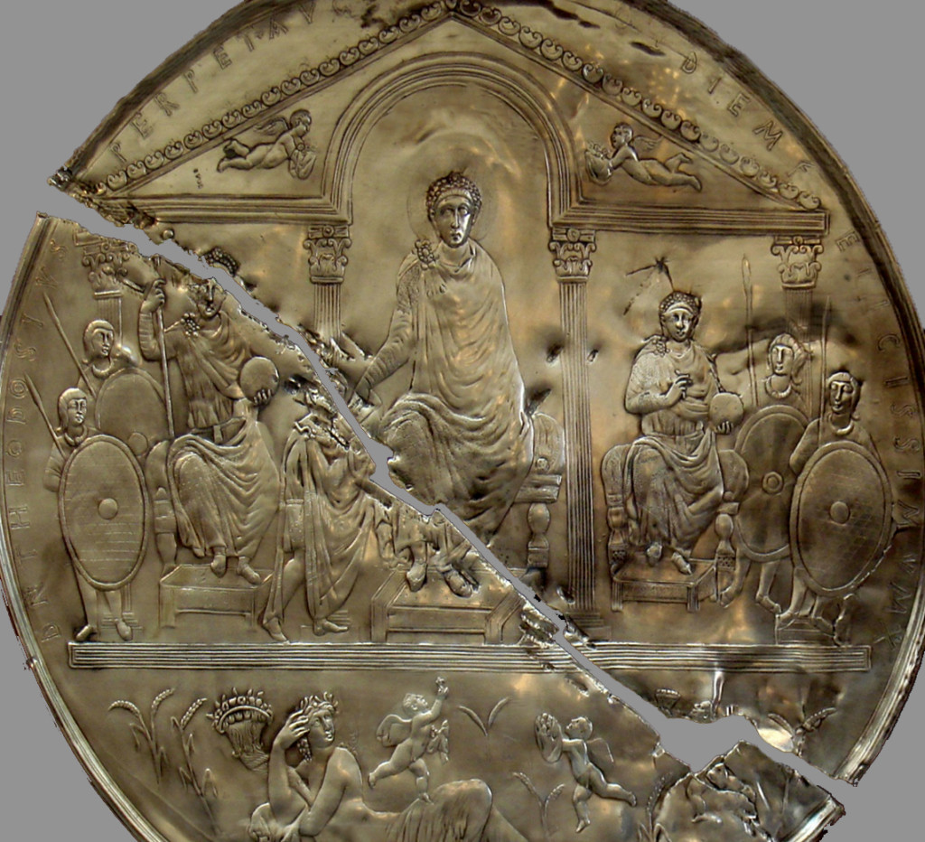 Modern replica of the Missorium of Theodosius (detail) in the Museum of Mérida, Spain. The missorium is broken in two parts, and the replica is as well. The disc features a regal figure in the middle who appears to be bestowing authority on a person kneeling before him.