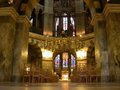 The interior has vaulted ceilings and all surfaces are made of polished stone. The photograph is angled at an alcove. There are stained glass windows in the rear of the alcove.