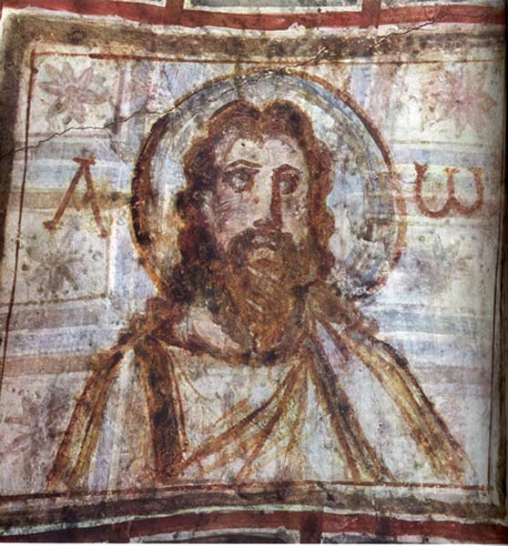 Typical painting of Christ with brown curled hair and a beard. He has a halo behind his head.