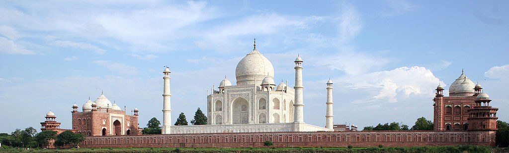 Photograph showing the entire complex of the Taj Mahal. The complex is made of three buildings. The center building is the most grand and pure white, while the other two are smaller and use red-brown brick along with white. The central building is framed by four domed towers atop a shorter fence: these are all white. The central building has a large dome in its center, and four domes on its corners. The front has a large archway leading to its entrance, and there are arched balconies on the ground floor as well as the second floor. Even at a distance, there is evidence of intricate carvings, especially on the entrance.