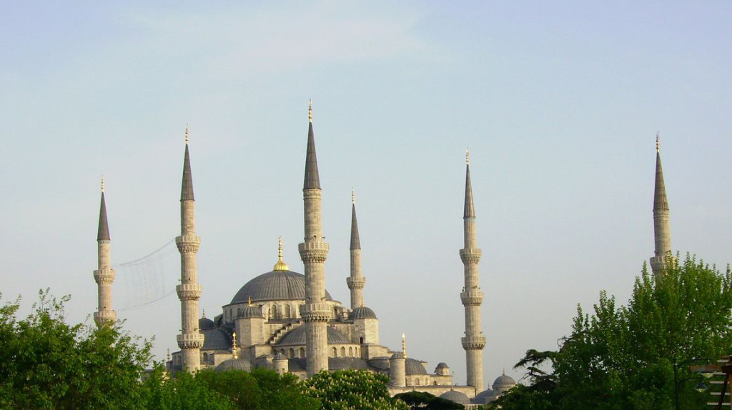 The mosque has a central dome topped with a golden steeple. It is in the center of several other domes varying in size and elevation. All the domes are blue, but the stone of the building is grey. There are six towers (minarets) framing the mosque; each topped with a point made of the same blue stone.