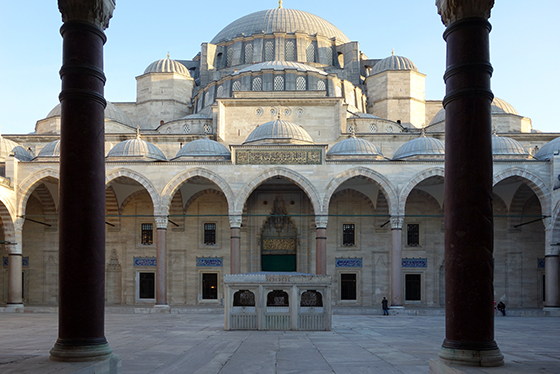 The photograph is framed with two columns in the foreground, illustrating the fact that the columns visible on the other side of the courtyard surround the entire interior. At the rear of the courtyard (the focus of the photograph) we see the main structure of the mosque. There is a central dome at the top, with two smaller immediately on either side of it. Below this is another dome shorter than the central dome, but approximately the same width; it is also framed by two smaller domes, though these are wider than the two above it. Just below this, there are several smaller domes covering the top of the courtyard's edge.