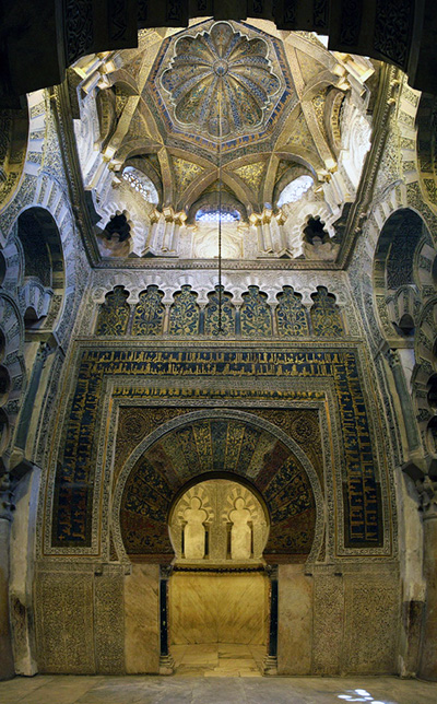 This photograph focuses on the interior of a dome. The walls leading up to the dome are incredible detailed and their repeating patterns are meticulously identical. The dome's symmetry is circular and is incredibly exact. The area is beautiful in its exactness.