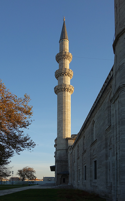 A simple minaret. There are three rings of balconies and the minaret is topped with a pointed blue roof.