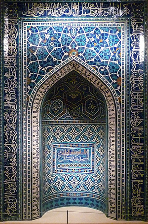 A prayer niche made up of blue, aquamarine, white, and gold tiles. The interior of the niche has arabic text and geometric patterns. The wall outside the niche has a rectangular frame outlining the arched niche entrance. Between the arch and the frame there is a geometric, almost floral pattern. Outside the frame there is more stylized arabic writing.
