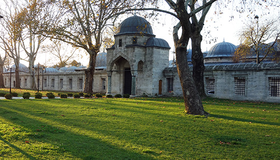 A long building that almost looks like a fence. The entrance has a dome with two smaller domes on either side of it. The entrance is preceded by a large archway.