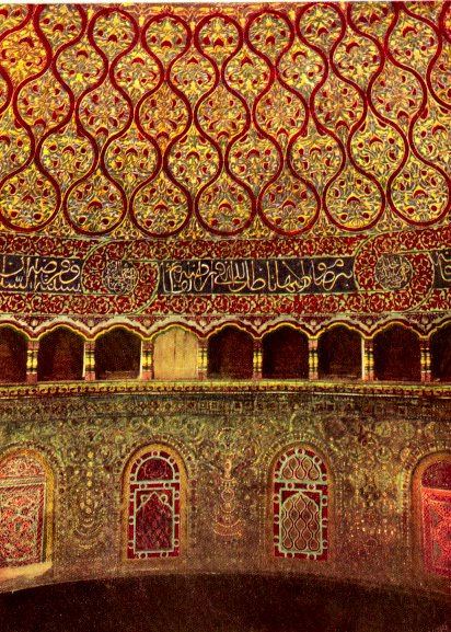 The interior is painted with reds and golds creating a very intricate pattern. There are arabic words along the bottom of the dome.