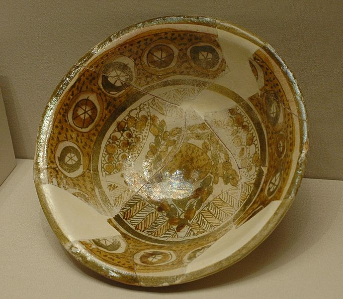 A broken bowl has been placed back together. The edges of the bowl have repeating circles, and the bottom of the bowl has a more intricate drawing on it.
