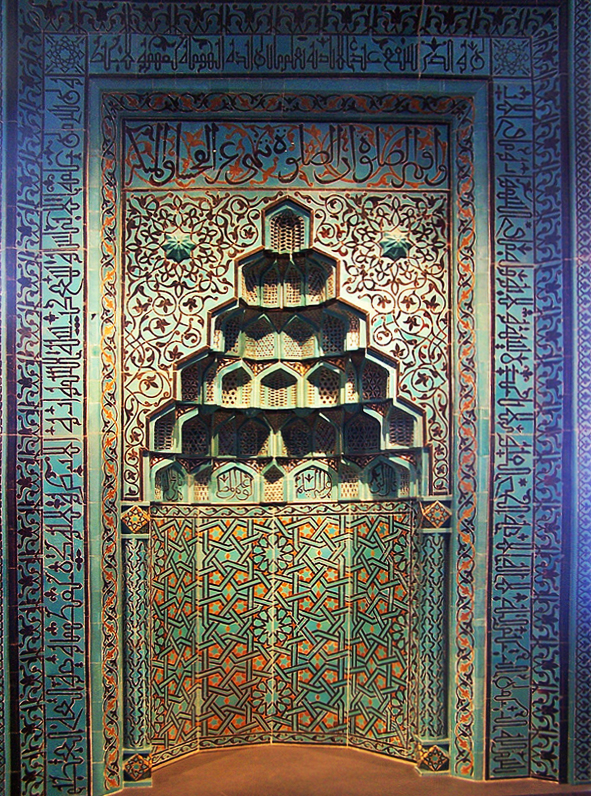 Intricate niche inset in a wall. The top niche is cut out in layers; It has an angled dome shape. The niche and surrounding walls are primary aquamarine with blue, maroon, and orange designs. These designs are geometric and include arabic writing.