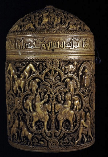 A cylindrical shape with intricate designs on the body and the lid. There is a band with writing between the two sections.