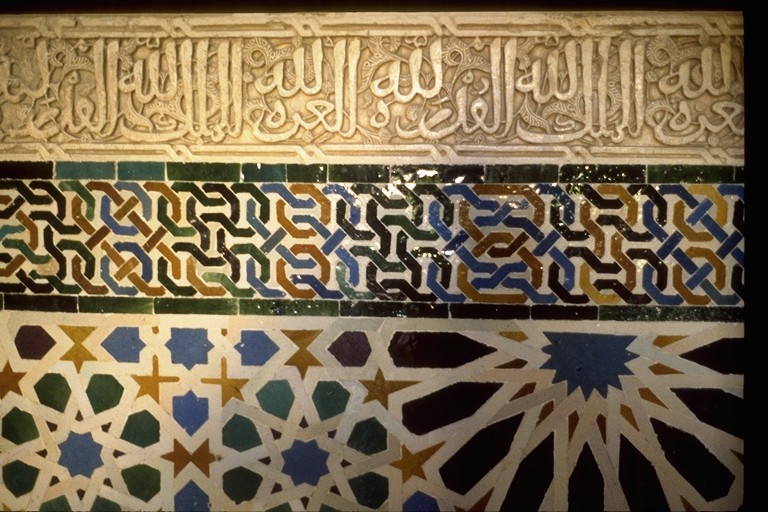 The wall is divided into three horizontal portions. The top has arabic lettering, the middle has a geometric knot pattern, while the bottom has a geometric, almost floral pattern.