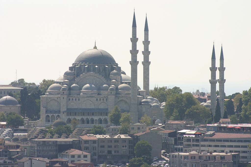 Mosque with the typical center dome and other surrounding domes. The minarets instead of forming a square around the mosque form a sort of rectangle to its side. The two minarets immediately next to the mosque are taller than the other two.