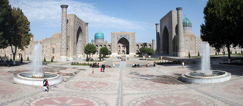 "A large paved courtyard with two large fountains in the foreground. The complex is almost completely symmetrical with fountains, trees, and archways reflected along a straight line. At the end of this ""line"" is the entrance to the Registan, which has a massive archway. On the roof of the building o the left of this entry is a large dome accompanied by a smaller dome. The building and complex are primarily constructed of muted colors, but the domes are vibrant aquamarine."