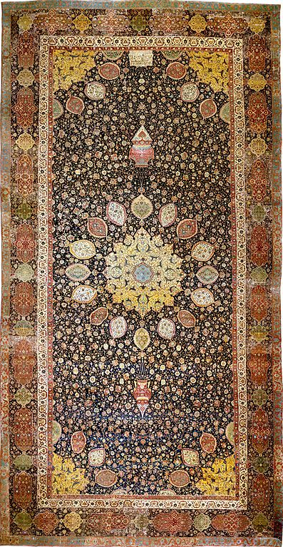 Intricate carpet with radial symmetry. The carpet is rectangular and the central radial pattern is framed by a border along the edges.