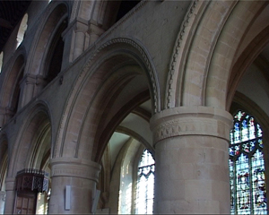 Interior walkway surrounded by smooth curved archways. On the exterior-facing wall, there are stained glass windows.