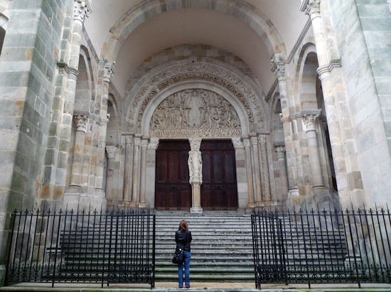 The majority of the cathedral's exterior is plain stone, but there is an intricate figure carved over the entrance, as well as one in between the two doors of the portal.