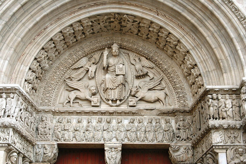 The carvings above the portal are extensive. Christ sits in the center, enthroned, with an angel, a winged lion, a winged ox, and an eagle.