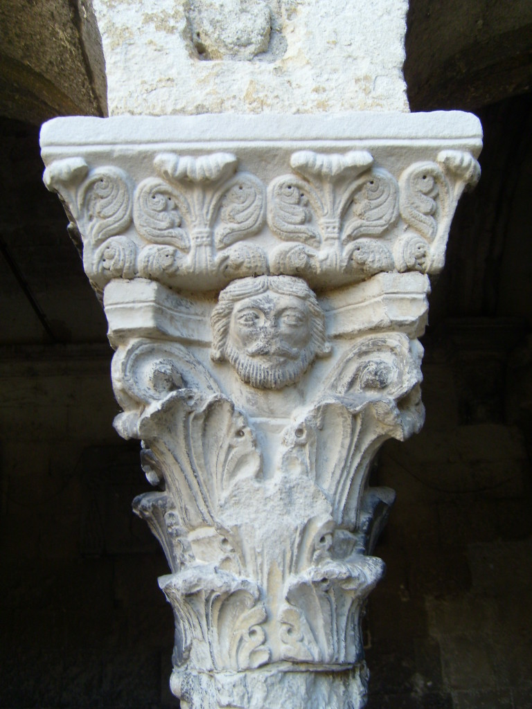 The capital features leaf patterns. There is also a face, worn away from time, just below the capital.